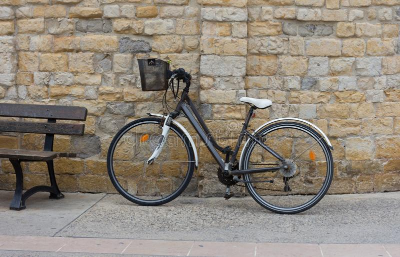 Bicycle with a Black metal basket propped against a stone wall. royalty free stock photo