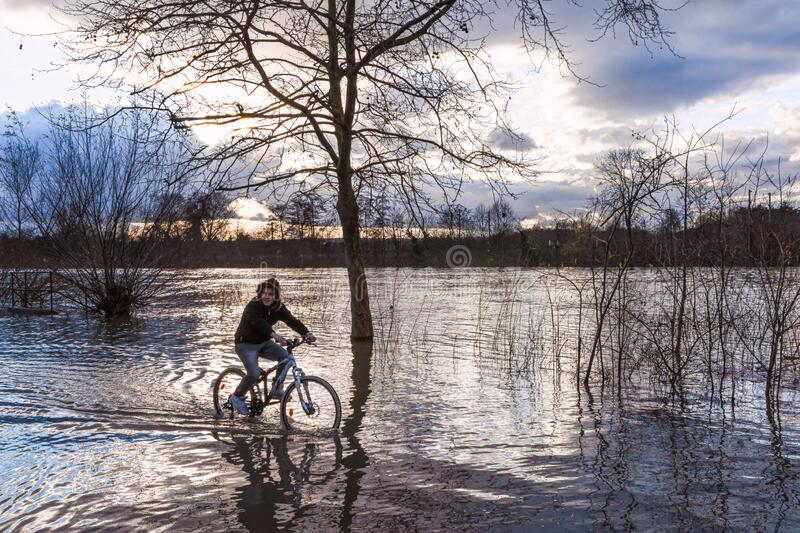 Bicycle boat during the flood. Young cyclist rolling on flooded docks on a winter evening