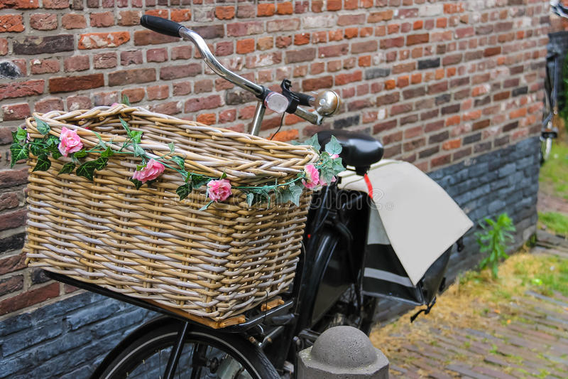 Bicycle com a cesta de vime decorada flor perto da parede de tijolo foto de stock
