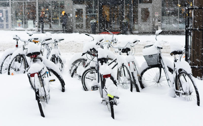 Bicycle completely covered with snow parked in central of Stockholm royalty free stock image