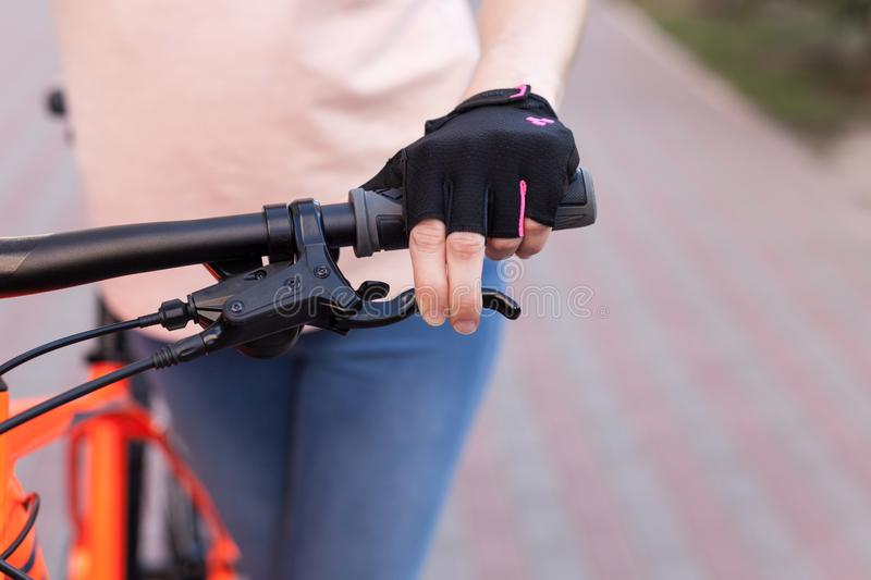 A girl in bicycle gloves holds her hand on the handlebars, clamping the brakes. stock photos