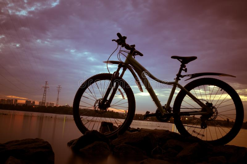 Bicycle in the evening, the sun above bicycle, with sunset and r royalty free stock photos