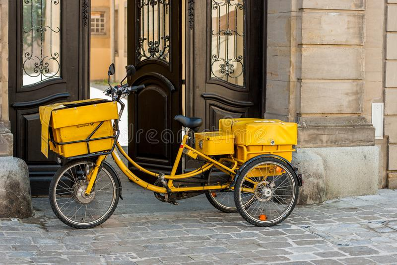 Bicycle of german post in front of a historical facade Bayreuth royalty free stock images