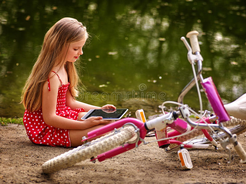 Bicycle girl recreation and watch tablet pc sits near water. royalty free stock photos