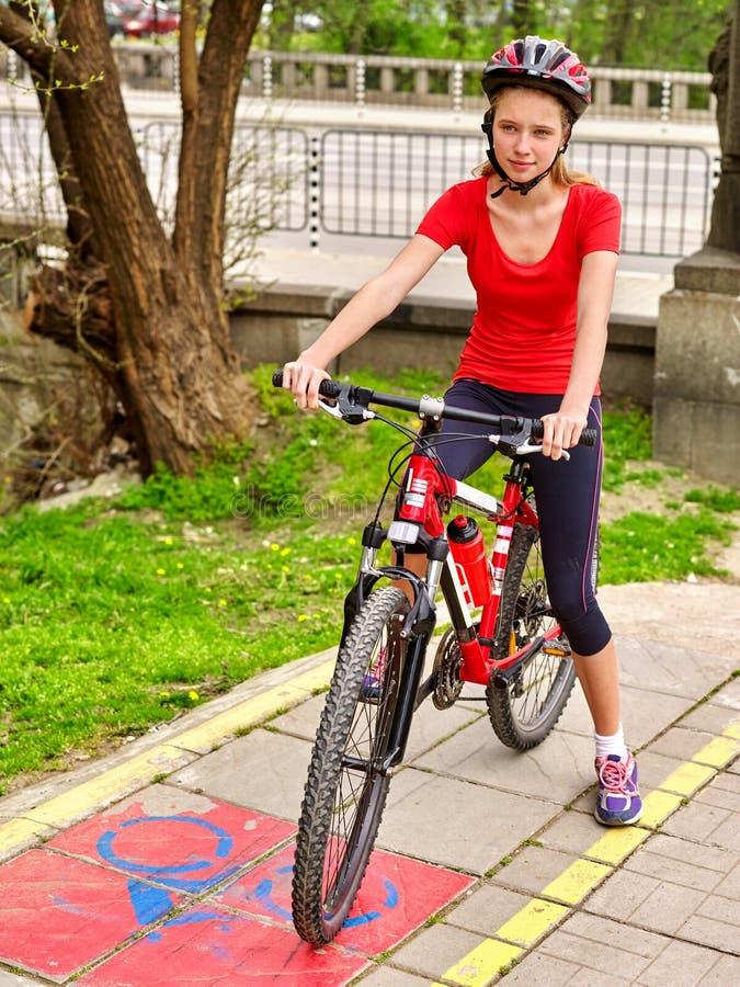 Bicycle girl wearing helmet and glass ciclyng . Bicycle girl. Girl wearing bicycle helmet and glass bicycle. Girls cycling on yellow bike lane. Bike share stock photo
