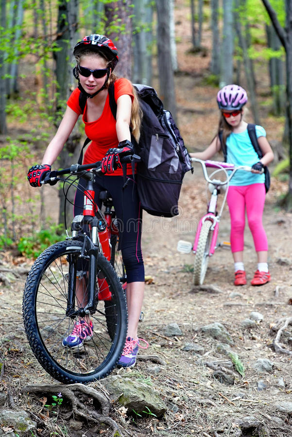 Bicycle girls with rucksack cycling in summer park. Bikes bicyclist girl. Girls wearing bicycle helmet and glasses with rucksack rides bicycle. Girls children stock images