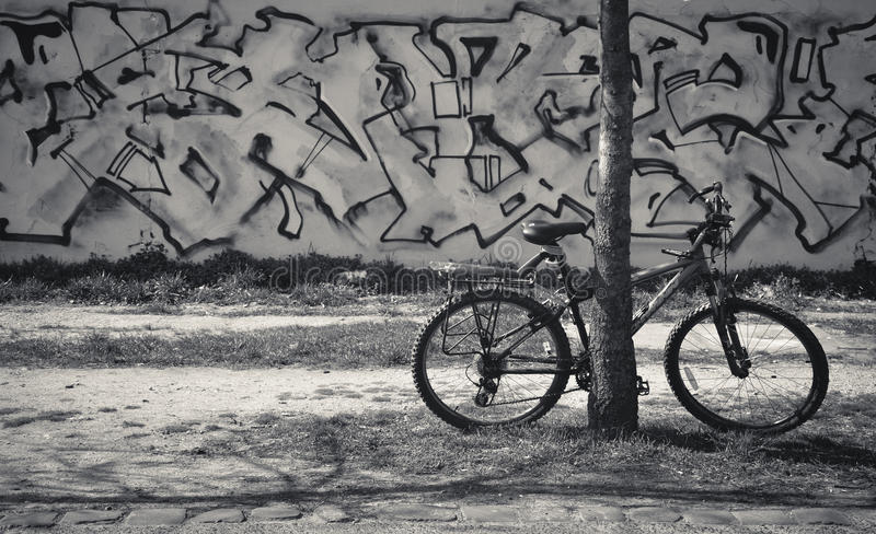 Bicycle on graffiti wall background in Black&White. Bicycle in foreground and graffiti wall in background. Black&White royalty free stock images