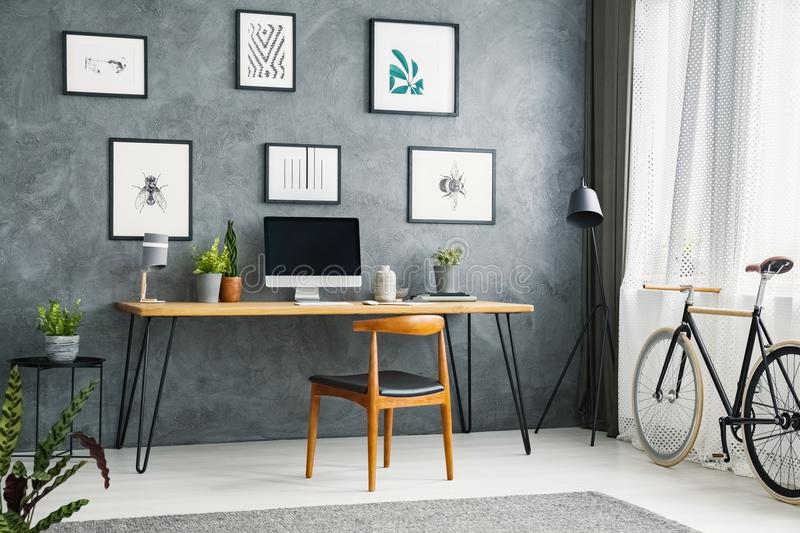 Bicycle in a grey home office interior with a wooden desk and ch royalty free stock photos