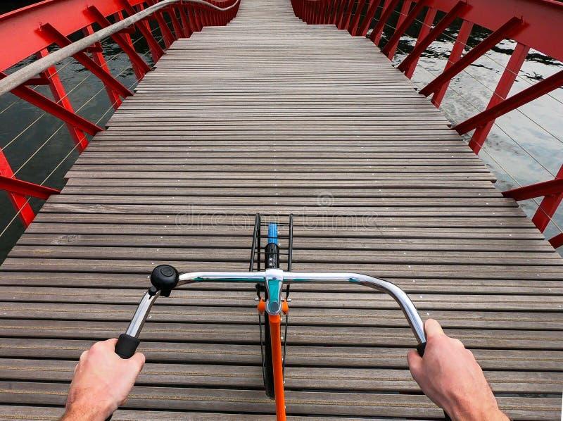 Bicycle handlebar POV view. Orange bike on the wooden red Python bridge in Amsterdam, Netherlands royalty free stock photo