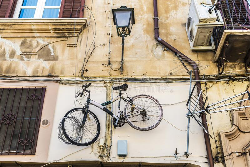 Bicycle hanging on an old wall in Palermo, Sicily, Italy. Bicycle hanging next to a television antenna on the wall of the facade of an old building in the old stock photos