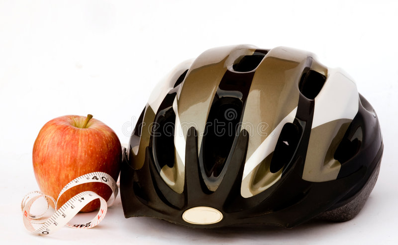 Bicycle helmet and apple. Bicycle helmet, meauring tape, and apple royalty free stock photos