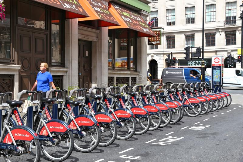 Bicycle hire station. LONDON, UK - JULY 7, 2016: Person walks by Santander Cycles bicycle hire station in West End, London, UK. The public bike hire network has royalty free stock image