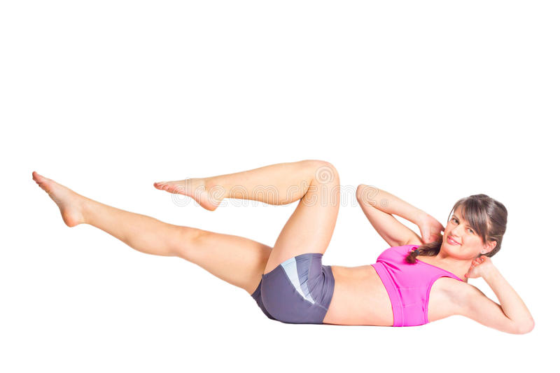 Bicycle kick. Active young woman doing bicycle kick exercise. Isolated on white background royalty free stock photo