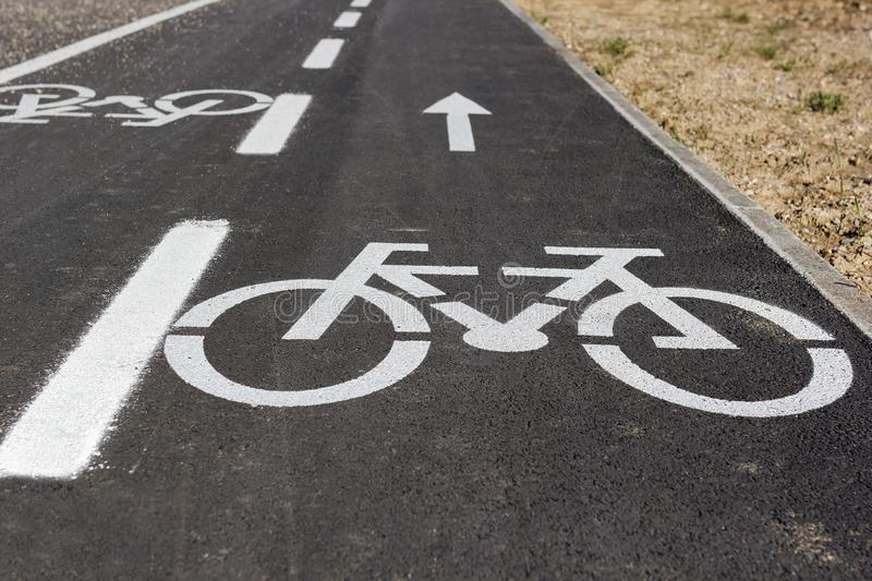 Bicycle lane with big white painted bike sign stock images