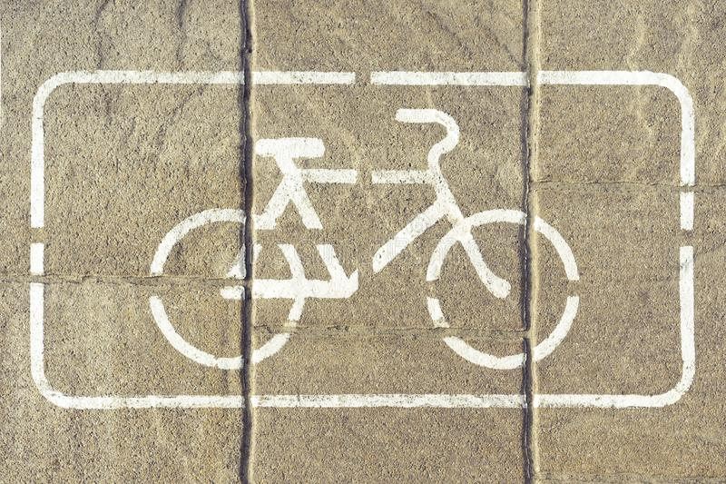 Bicycle lane. Bike path with a symbol of a white bike in a white rectangle. Bicycle sign on gray asphalt pavement, close up view royalty free stock photo