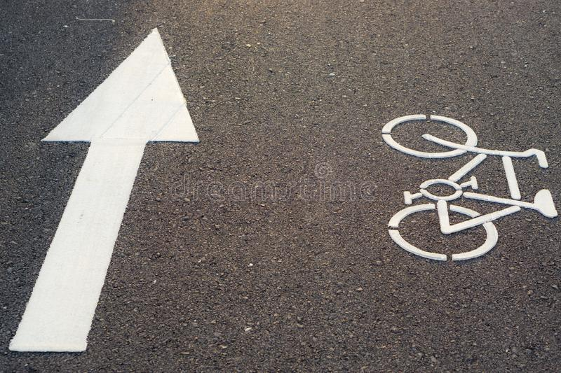 Bicycle lane marking or bike road sign with an arrow on the street in the public park royalty free stock images