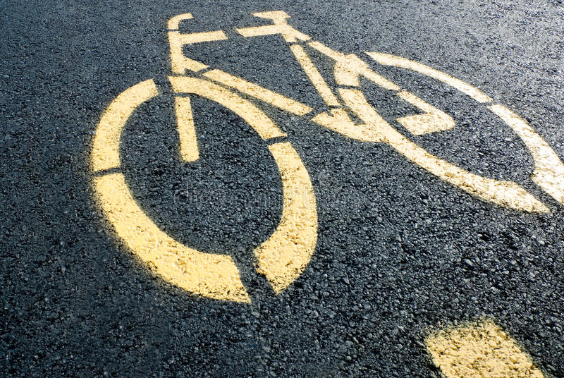 Bicycle lane sign on road. Pathway for bicycle with yellow bicycle lane sign on road stock image