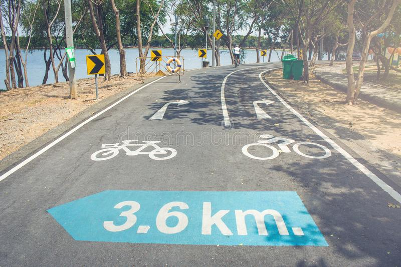 Bicycle lane with traffic signs on road flanked with green trees in Nong Bon Water Sport Center. Selective focus stock photo