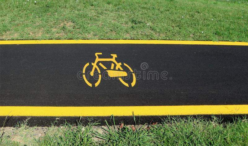 Bicycle lane with yellow bicycle symbol on asphalt, two yellow lines on the borders and grass on both sides. stock images