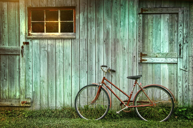 Bicycle leaning against grungy barn royalty free stock photo