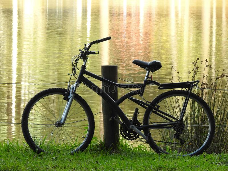 A bicycle leaning against a fence on the edge of a lake at dusk. A bicycle leaning against a wooden fence post on the edge of a lake at dusk. The waters reflect royalty free stock photos