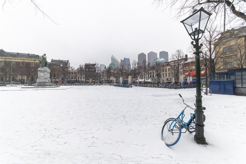 Bicycle locked with the lamp post with copy space. Bicycle locked with the lamp post at the central place covered by snow, Plein Dutch, usually crowded with royalty free stock image