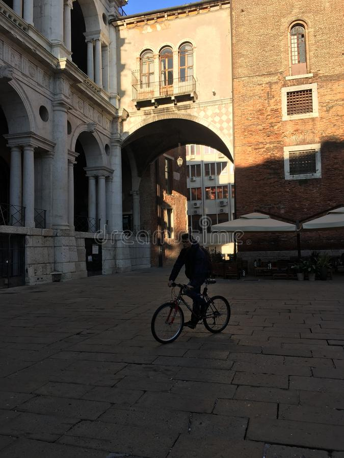 Bicycle man under a bridge in Rome stock photography