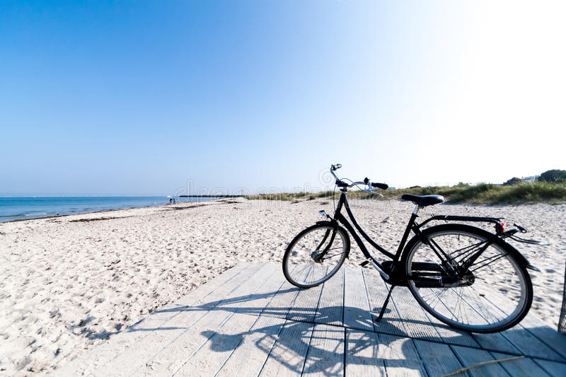 Bicycle on Marienlyst Beach in Helsingor, Denmark. A black bicycle on Marienlyst beach in Helsingor, Denmark, on a beautiful sunny day with clear blue skies. The stock photo