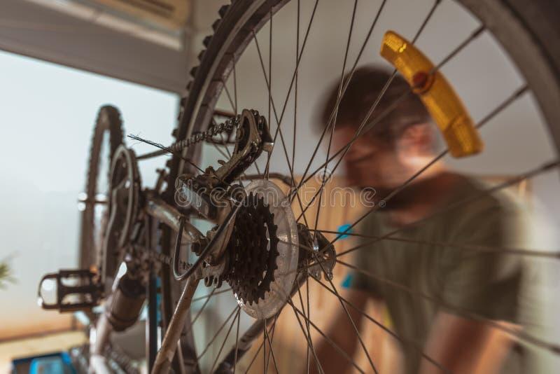 Bicycle mechanic repairing old mountain bike in workshop stock image