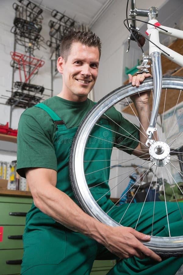 Bicycle mechanic repairing wheel on bike in a workshop royalty free stock images