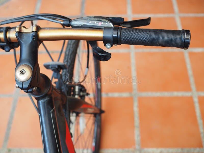Bicycle o aperto de guiador dourado da mão no assoalho de telha imagens de stock royalty free