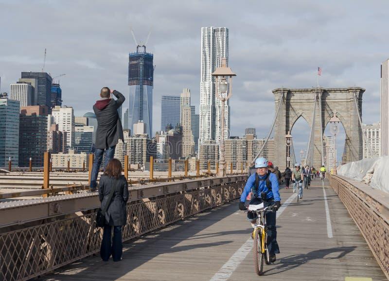 Bicycle os cavaleiros e os turistas que apreciam um dia na ponte de Brooklyn foto de stock royalty free