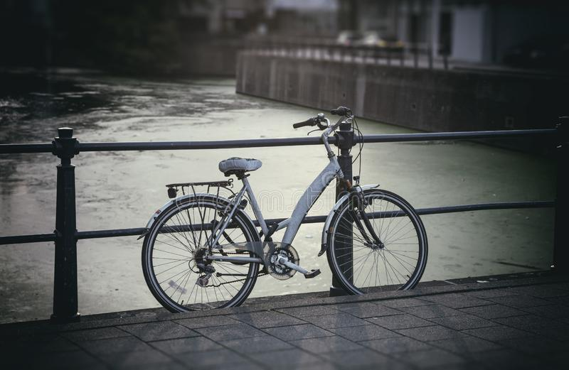 Bicycle parked on bridge over city river, blurry background. stock photo