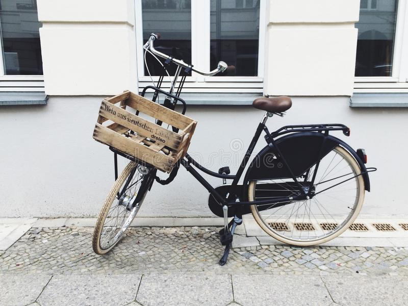 Bicycle parked on footpath. Black bicycle with wooden crate parked on footpath in Mitte area of Berlin, Germany royalty free stock photo