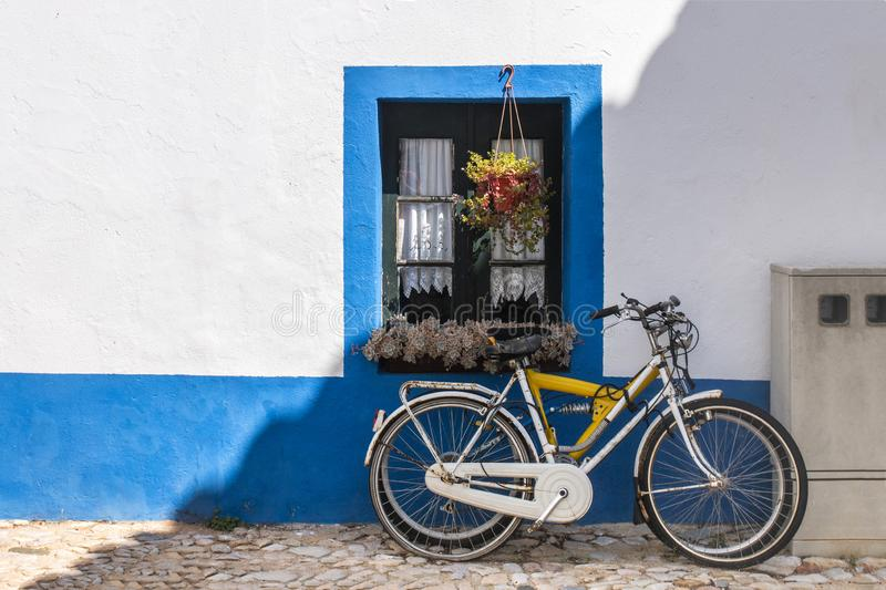 Bicycle parked near house. Typical european view of a bicycle parked near house painted with blue and flower vases royalty free stock photography