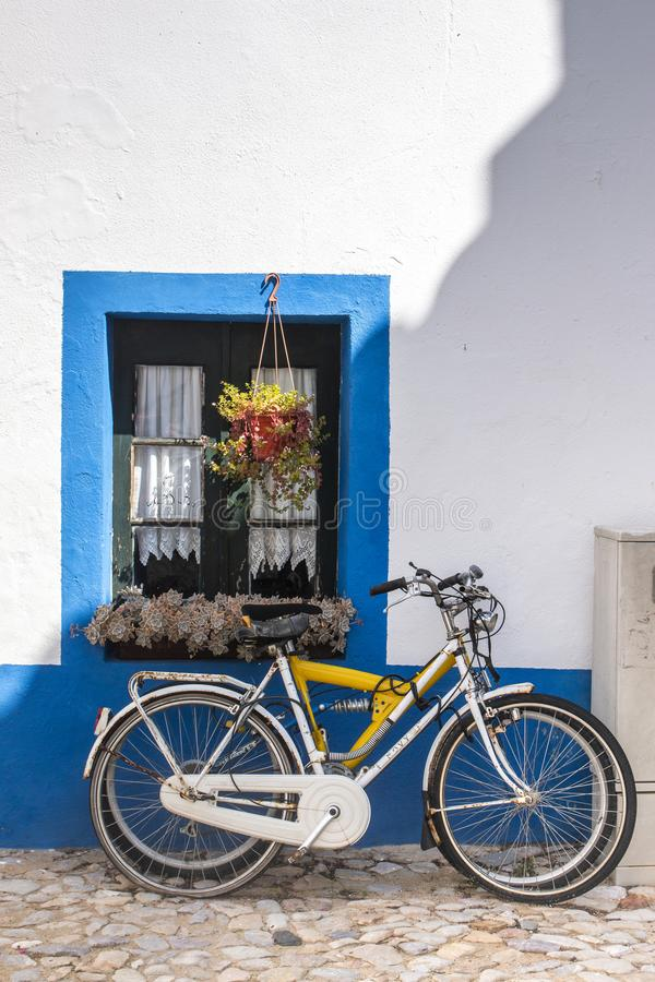 Bicycle parked near house. Typical european view of a bicycle parked near house painted with blue and flower vases royalty free stock image