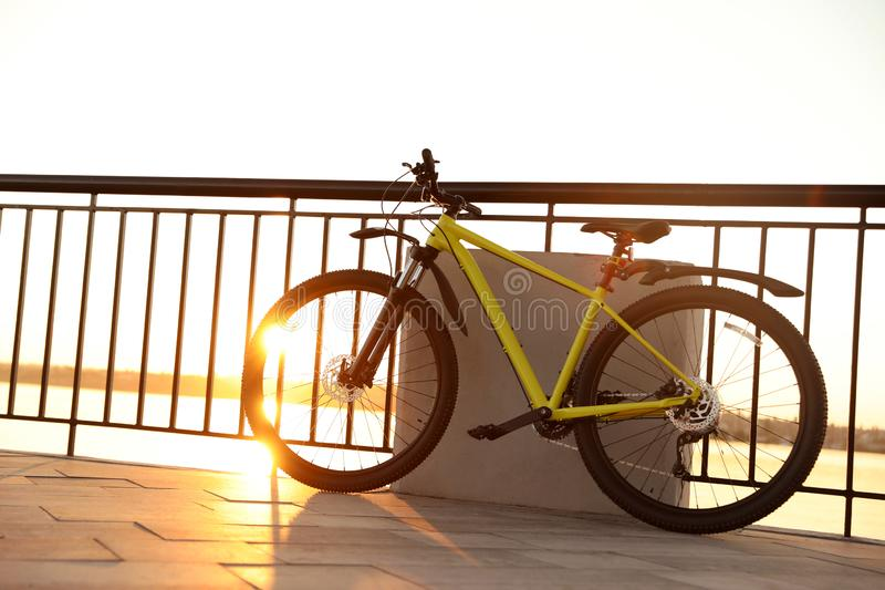 Bicycle parked near railing on city waterfront at sunset. Yellow bicycle parked near railing on city waterfront at sunset stock photo