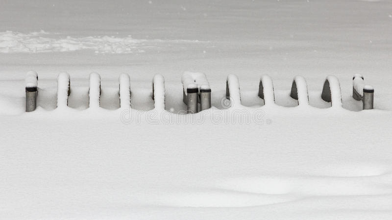 Bicycle parking covered with snow. A bicycle parking place in the park covered with fresh snow stock photos
