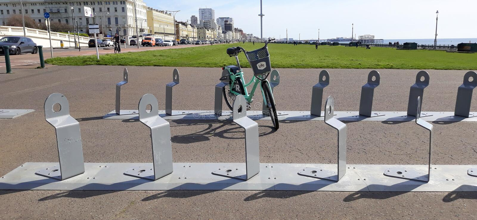 Bicycle parking at Hove Lawns. A bicycle parked on the bicycle parking lot on the row for public hire bikes at Hove Lawns seafront in Hove, Sussex, England royalty free stock image