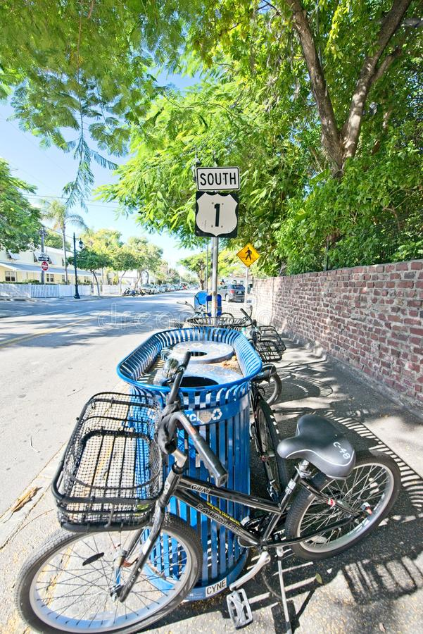 A bicycle is parted beside a trash can on South Highway 1 in Key West Florida. A bicycle with a basket is parked near a trash can on South Highway 1 in Key West stock photo