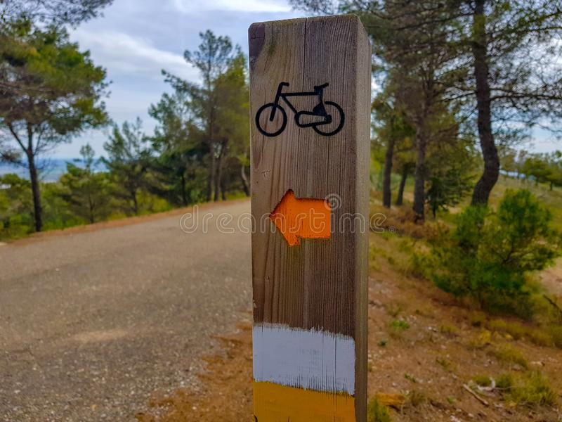 Bicycle path through the park, the sign on a wooden landmark nailed to the ground with forest background and people with backs to. Walk asphalt blue curve royalty free stock images