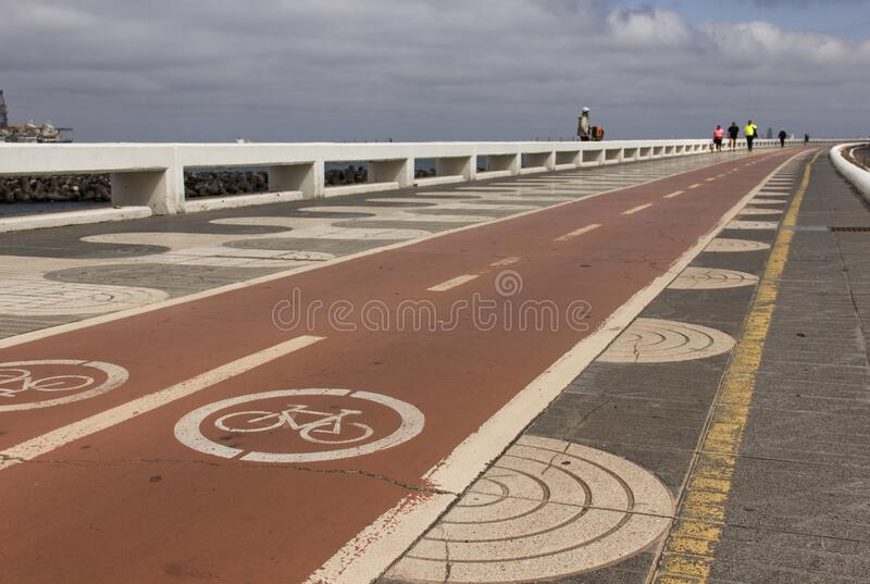 Bicycle red lanes in Las Palmas, Spain. Bicycle red lanes next to pedestrian sidewalk on the coast in Las Palmas, Spain. Outdoors activity, healthy environment stock photos