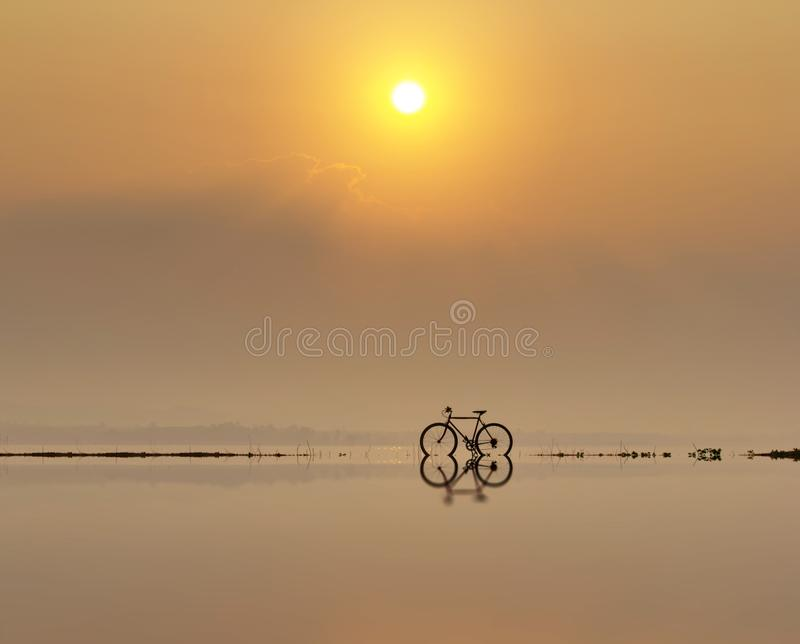 Bicycle reflection on water with sunset or sunrise. Background royalty free stock photos
