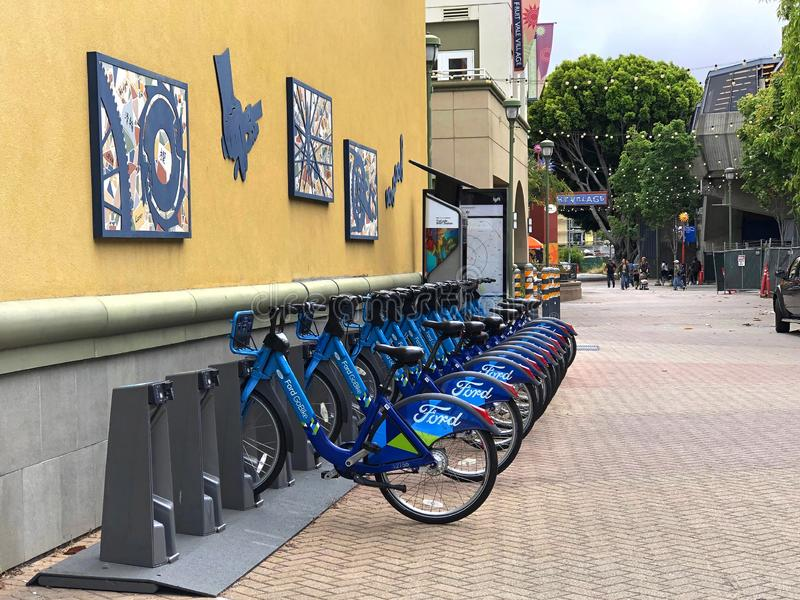 Bicycle rental station at Fruitvale Bart in Oakland, California. Fruitvale, CA - June 26, 2019: Blue Go Ford shared bikes lined up in the at Fruitvale BART stock photography