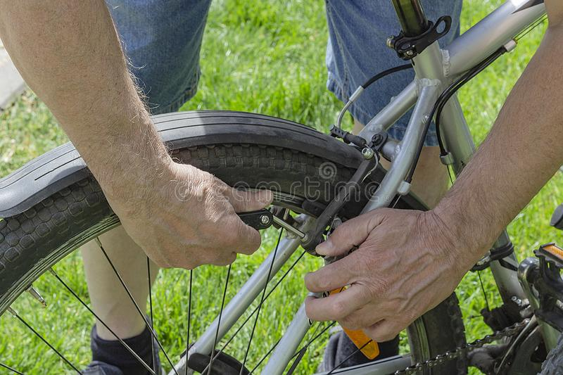 Bicycle repair. Close-up of a man`s Hand with a tool. stock image
