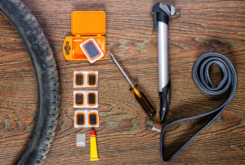 Bicycle repair kit, wheels camera on a wooden background. Bicycle repair kit, wheels camera on wooden background stock image