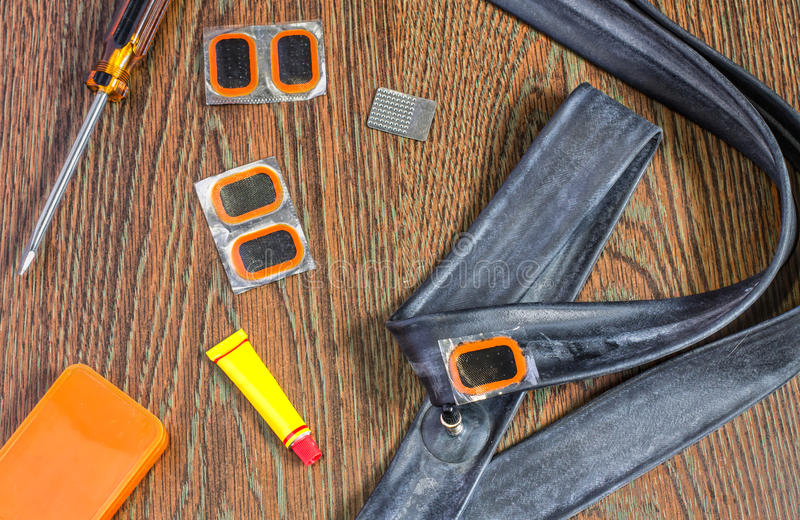 Bicycle repair kit, wheels camera on a wooden background. Bicycle repair kit, wheels camera on wooden background royalty free stock images