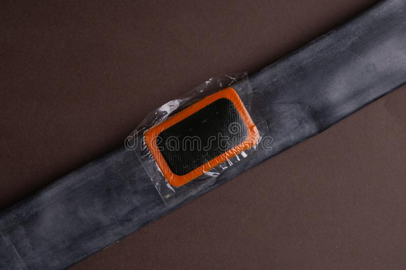 Bicycle repair kit, wheels camera on wooden background. Patch on the camera of the bike. Patch on the camera of the bike. bicycle repair kit, wheels camera on royalty free stock image