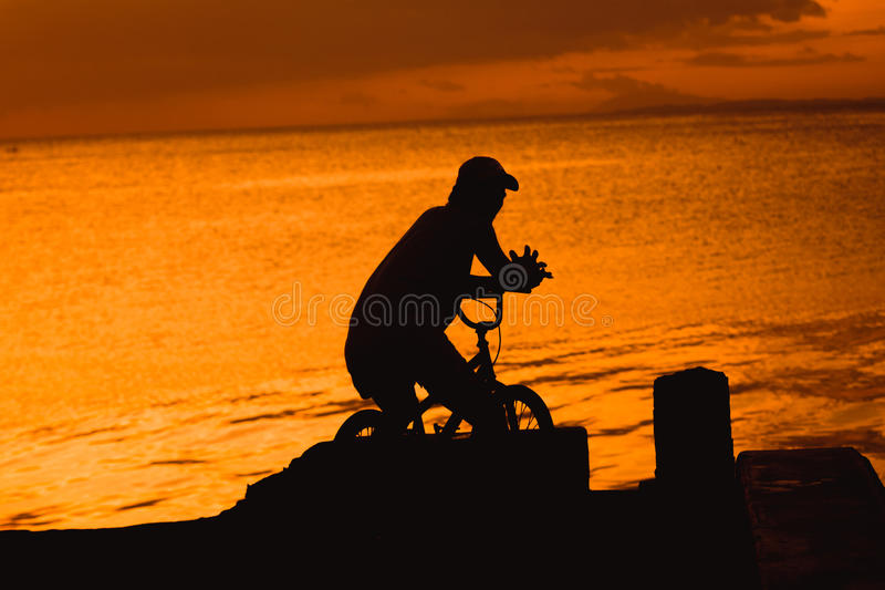 Bicycle ride along the sunset stock images