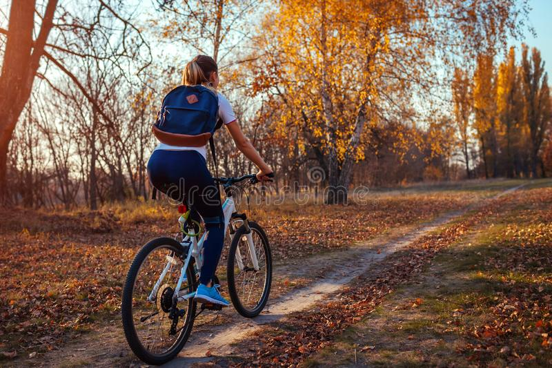 Bicycle ride workout in autumn park. Young woman biker riding a bike in fall forest. Healthy training. Bicycle ride workout in autumn park. Young woman biker stock photo